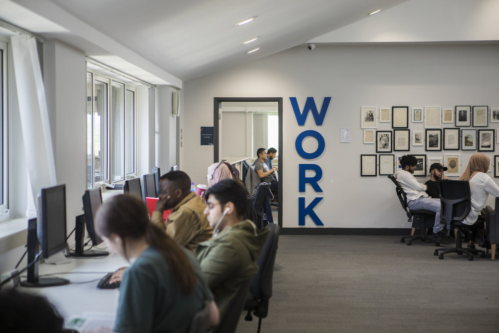 A shot of one of the computer areas in our Clifford Whitworth Library. The walls are freshly painted white but at the back you can see some art and photography framed on the wall next to students who are sat in black chairs at a table. The word 'Work' is fixtured on the wall in blue writing vertically. In the foreground you can see students sat at computers that are in front of windows.
