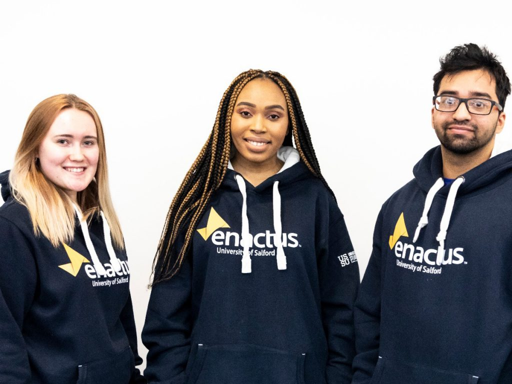 Three other students involved in Enactus. All three of them having the navy Enactus logo hoodies on. They are stood facing the camera and smiling.