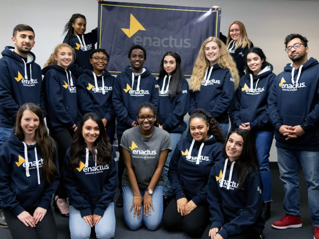 Members of the Enactus society all wearing navy blue hoodies with the 'Enactus University of Salford' logo on. Two students at the back of the group photo hold up a banner with the logo also on.
