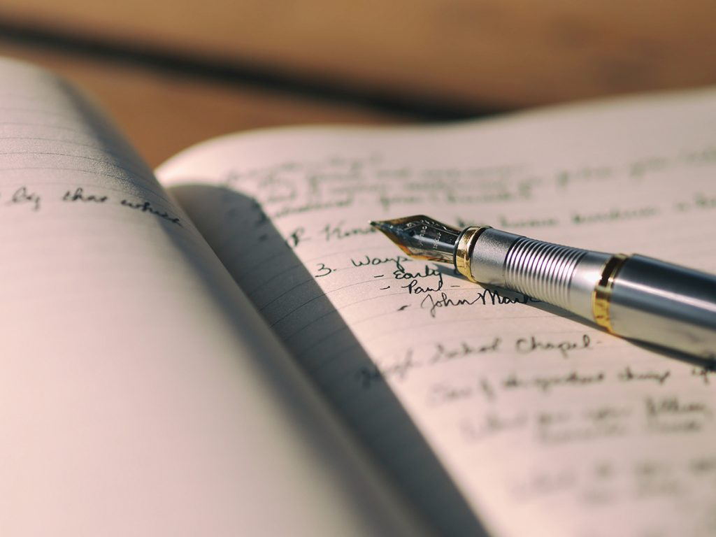 A gold and silver fountain pen sits on top of a lined notebook that has a lot of writing in it.