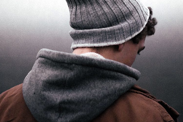 In the foreground of a gradient grey background stands a man with his back facing to the camera wearing a grey beanie and dark clothes.