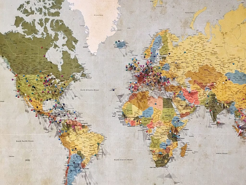 The map of the world with a couple of pins stuck in particular places that the owner must have visited.