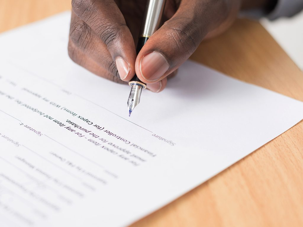 A man is using a fountain ink pen to sign a contract or document of some form which sits on top of a wooden table.