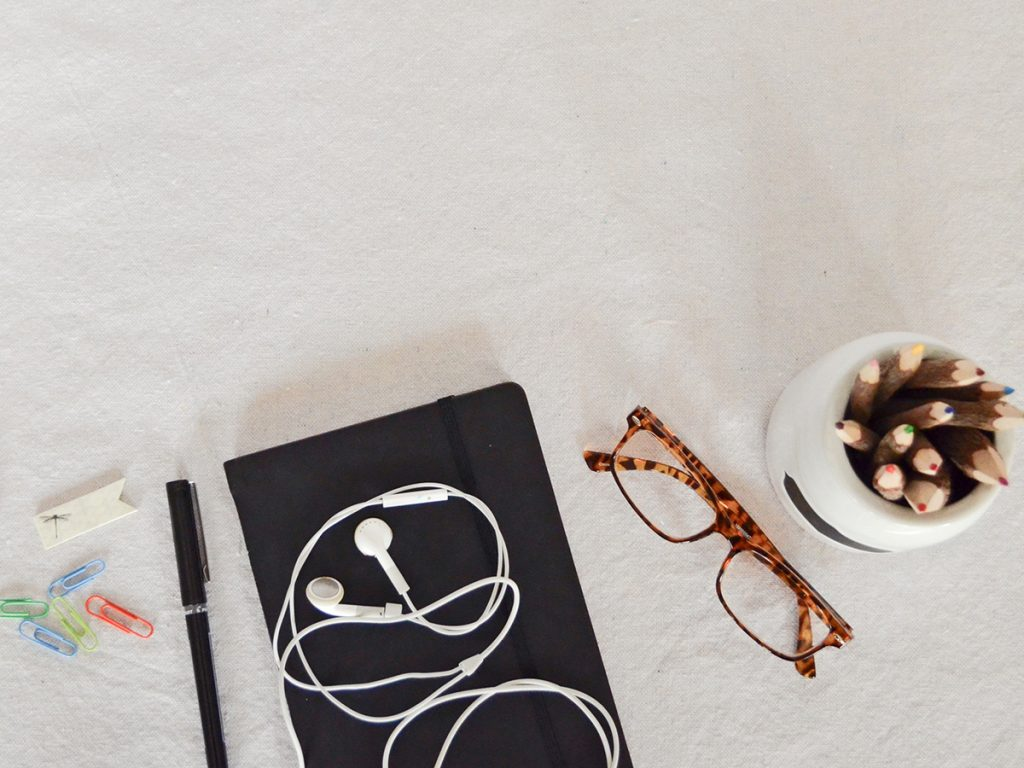 A black notebook sits on a white table with white headphones tangled on top. On the left next to it, is a black pen and some assorted colour paper clips. On the right of the notebook is a pair of glasses and a pot full of sharpened coloured pencils.