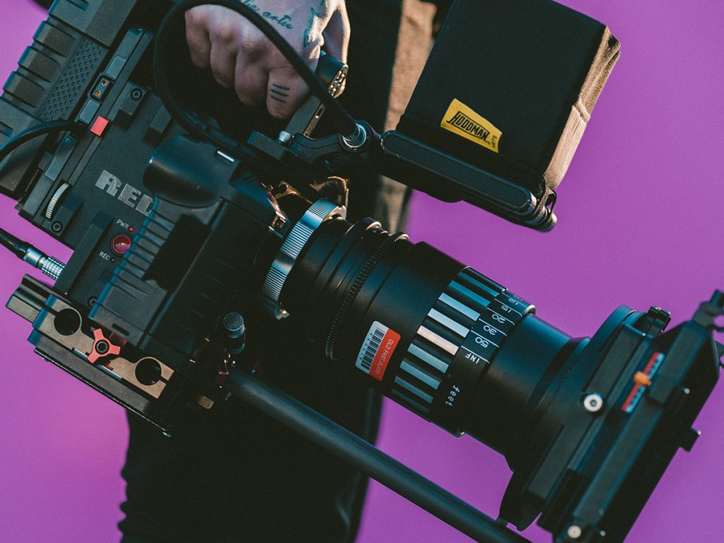 Against a bright purple background, a person with hand tattoos holds a large black camera video recorder