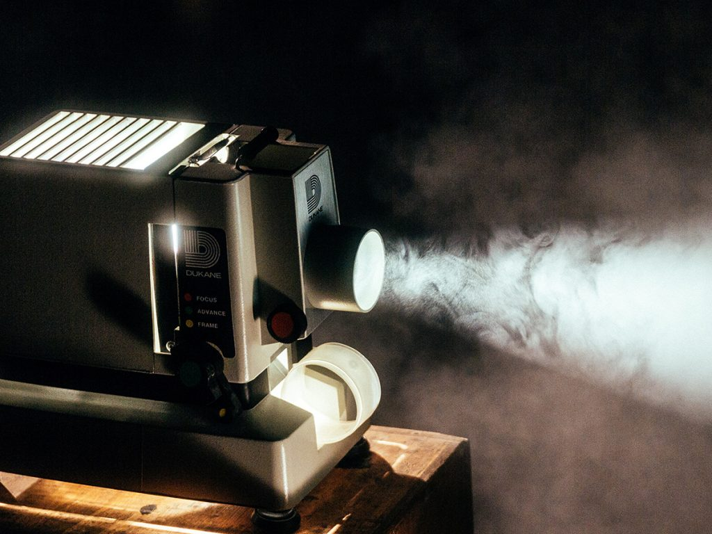 A Dukane projector sits on a wooden table. It is turned on projecting light forward.