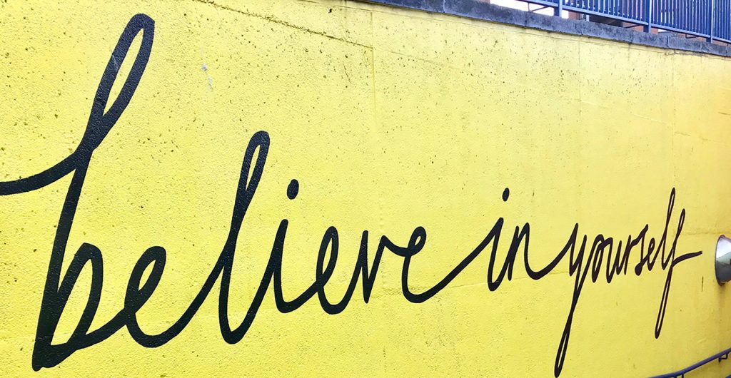 street art that reads 'Believe in yourself' in cursive