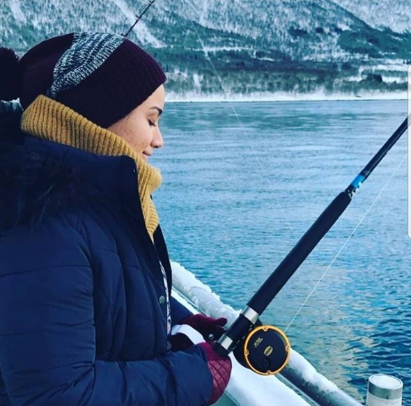 A photo of Marwa wearing a striped knitted beanie, a yellow scarf and navy coat with a fishing rod looking out to a cold looking lake.