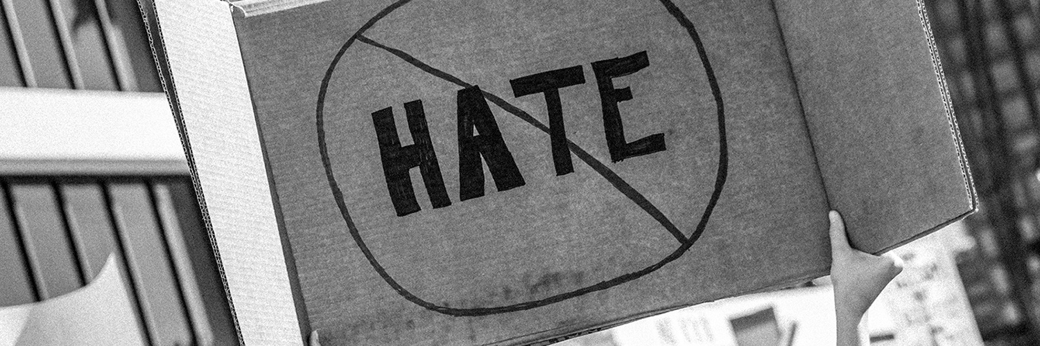 Taken or edited in black and white, someone is holding up a cardboard protest sign that shows the word 'HATE' crossed out to represent being against hate crimes