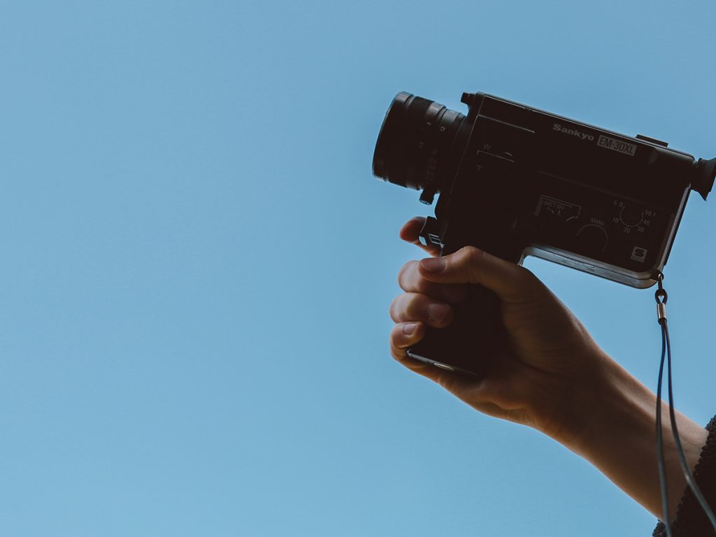 A person holds up a small Sankyo EM-30XL camera recorder with a blue sky background.