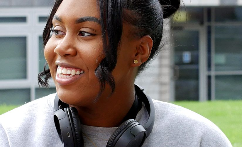 Artiana is sat in front of the New Adelphi building wearing a grey jumper and black headphones around her neck. She is looking into the distance and smiling.