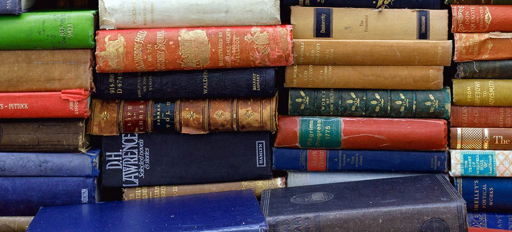A pile of various hardback books of different colours including reds, blues, browns and green.