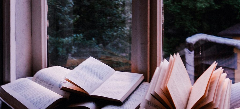 On a pale white windowsill there is a pile of opened hardback books scattered across the surface. The pages are different shades of clean white or slightly tinged with an beige colour from the sunlight.