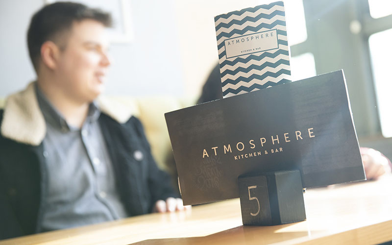 A photo taken at an angle that puts one of the table number stands at Atmosphere Kitchen and Bar as the main part of the shot. The table number is 5 and it's holding two menus that both read 'Atmosphere' on them. At the table in the background you can see a group of people sat chatting at the table.