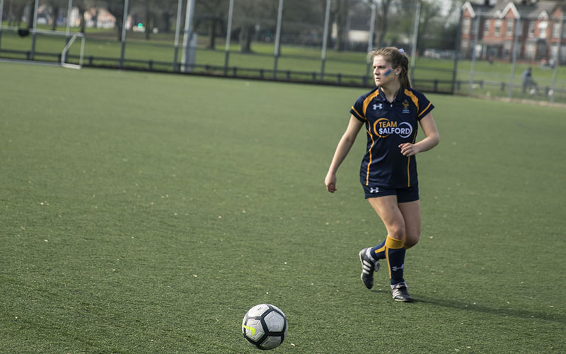 A photo of a girl playing football taken on a green grassy pitch in the Spring. The weather is nice and looks sunny. The girl is wearing a 'Team Salford' football kit which consists of colours navy blue and yellow. She also has blue and yellow face paint stripes on her cheeks. She looks like she is gearing up to take a kick of the football.