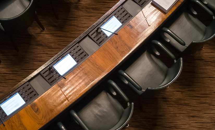 An up-top shot of several black armchairs in front of wooden desks, set out like a meeting room or parliamentary discussion.