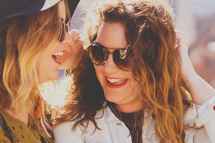 Two women one in sunglasses and one in sunglasses and a hat smiling and laughing together.