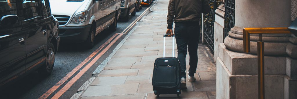 A photo of a person walking down a street pulling a black wheeled suitcase behind him.