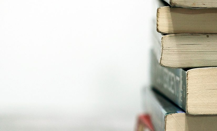 On a white background, a stack of books sits on a desk, the bottom ends of the books facing the camera.