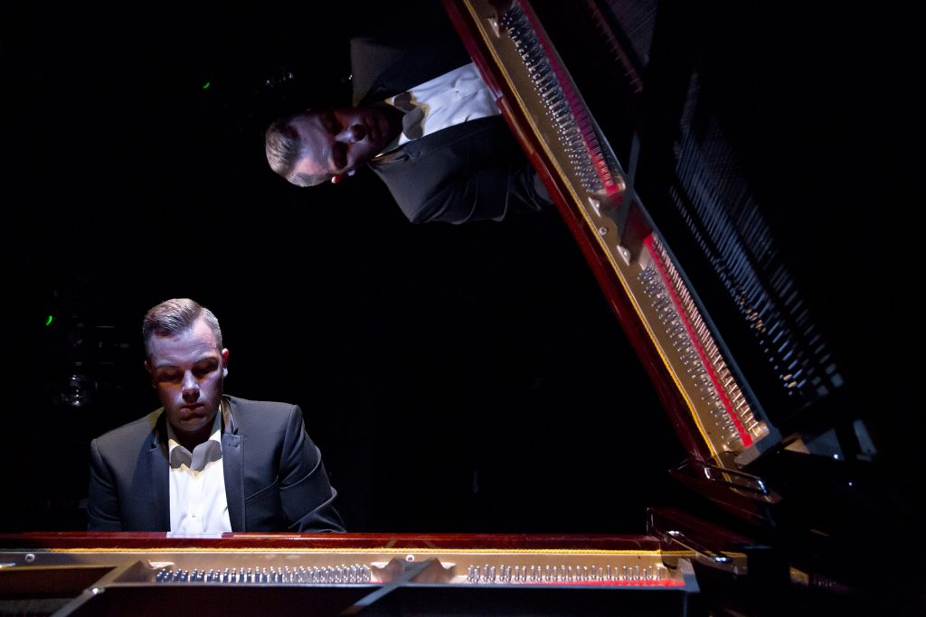 Nicholas McCarthy is sat in a black suit playing the piano.