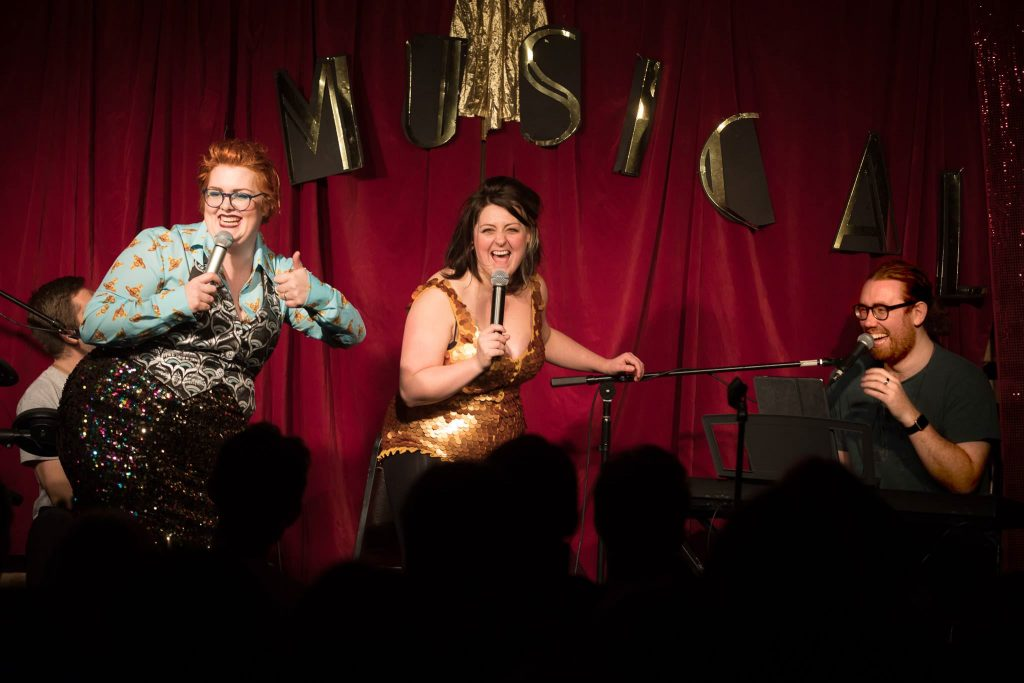 Upon a red curtain background is the word 'Musical' cut out and stuck up in gold cardboard. On stage is a man with ginger hair and glasses performing on a keyboard with a microphone. Kiri Pritchard-Mclean and Jayde Adams are also on stage with handheld microphones having a good time performing.