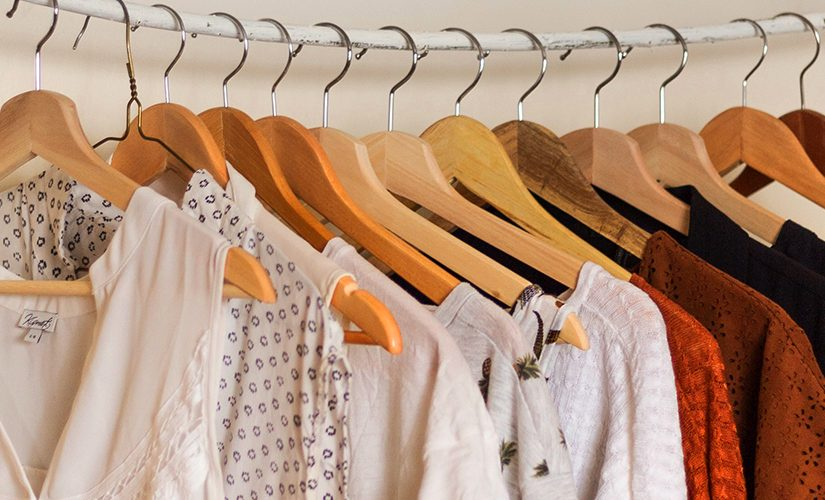 Several pieces of clothing are hung with clothes hangers on a rail