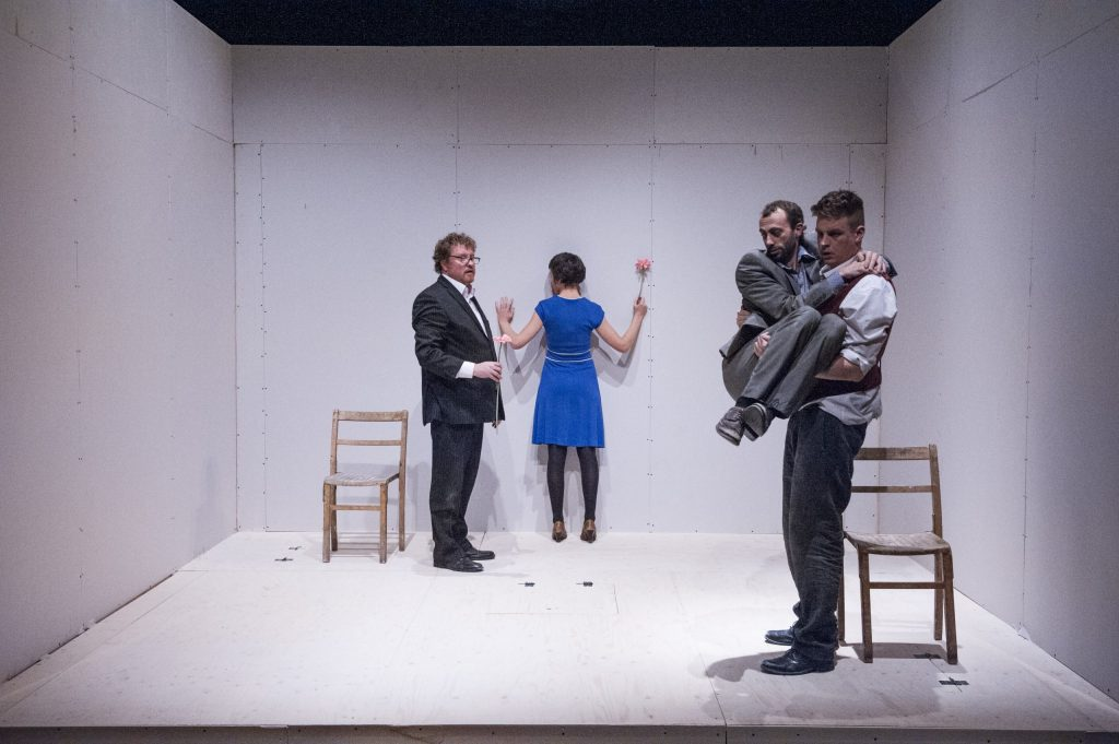 Four performers are in a white square room, one wooden chair placed near the back on the left side and another chair placed near the front of the square room on the right side. A lady performer holding a flower in a blue dress stands at the back, holding her arms up against the wall, next to her is a man with curly hair and glasses also holding a flower. This man watches two men near the front, one who is stood up in a waistcoat and suit, he is holding a man in a grey suit like a child - their actions are similar to as if the man being held has been something scary on the floor and he has jumped up in fright.