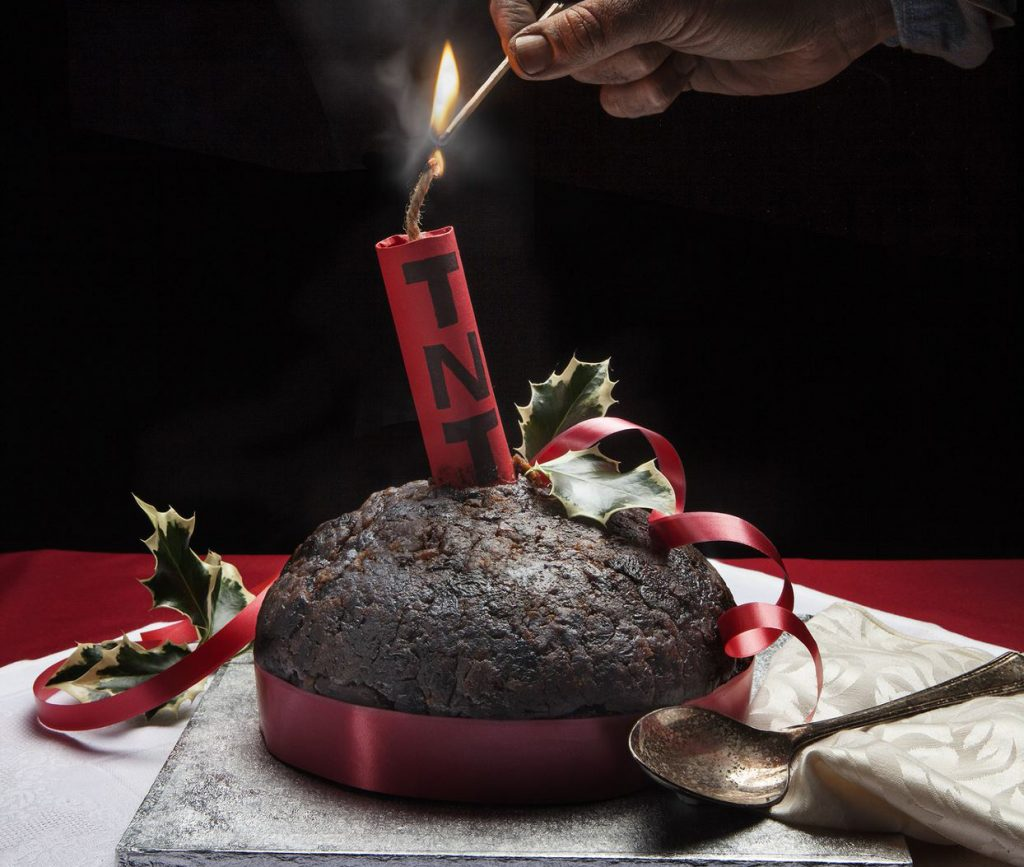 On a table with a red cover sits a christmas pudding that has a red ribbon around the base. A comical stick of red tnt has been put in the pudding and it being lit with a match by a hand.