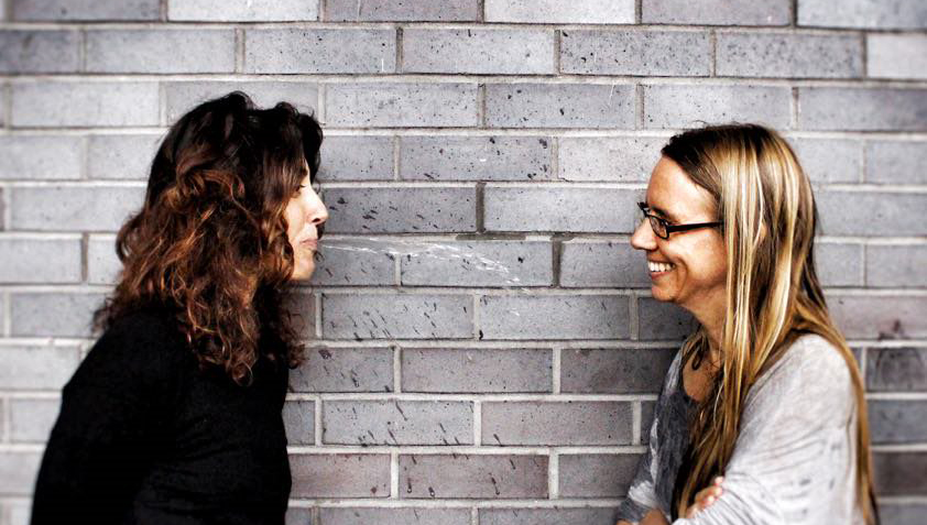 Two women are stood facing each other next to a grey brick wall. The woman on the right has black glasses and long straight dark blonde hair. She is grinning. The woman on the left has curly brunette hair and a black jumper. She looks like she is smiling or on the edge of laughing.