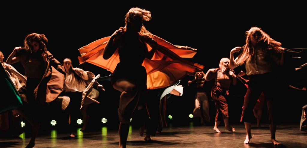 On a stage with warm lights at the base, several dancers in orange and brown clothing are performing on the stage. They are doing twirls and movements that encourage their outfits and hair to create structure on the stage (e.g. windswept, fan movements)