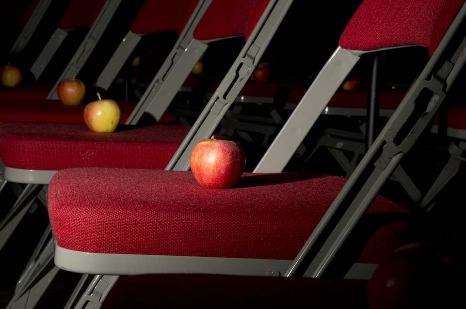 A close up shot of a row of red fold out chairs. On each red chair cushion there is an apple placed in the centre.
