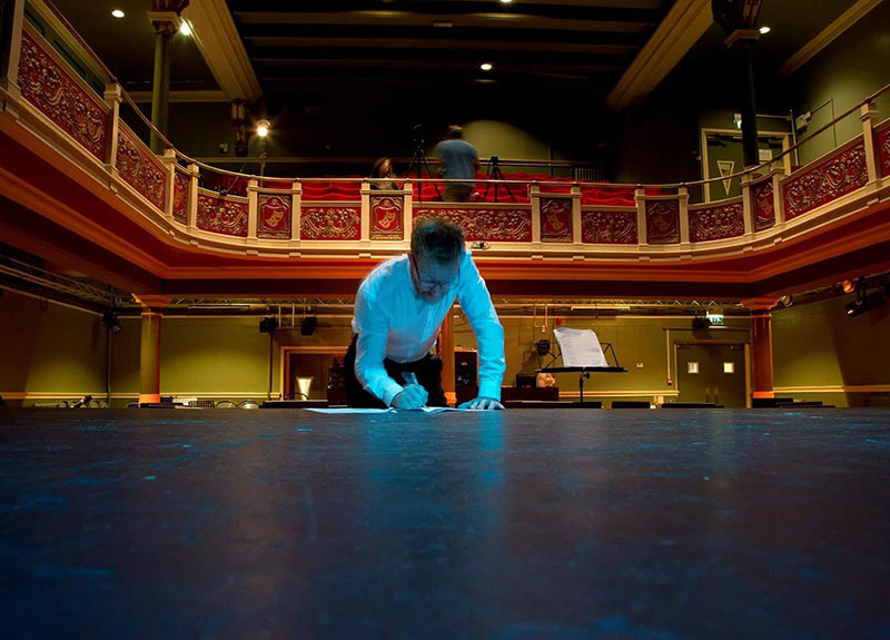 An image portraying the planning process behind Concerto. Someone is sat on the stage floor, writing in a notebook whilst backstage staff work within the seating area with cameras.