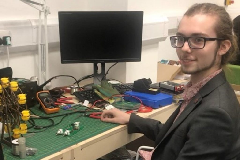 Ivan Holmes posing with his computer and electronic equipment