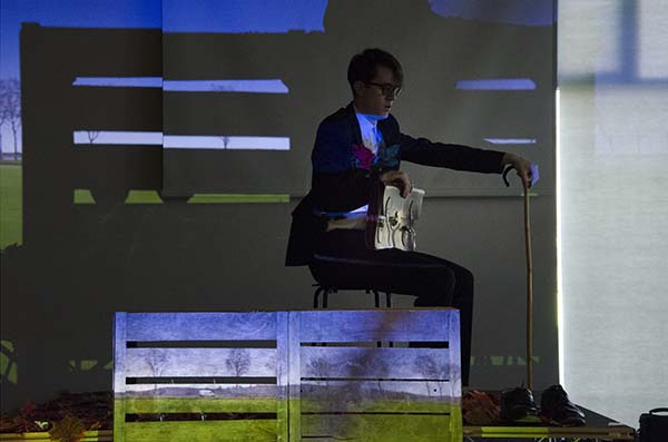 A suited performer sits on stage in front of wooden planks. He is holding on to a walking stick with a briefcase perched on his lap.