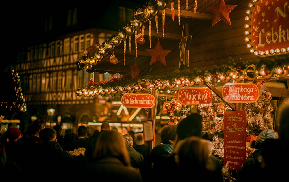 A photo shows German Christmas Markets lit up at night with a big crowd of people.