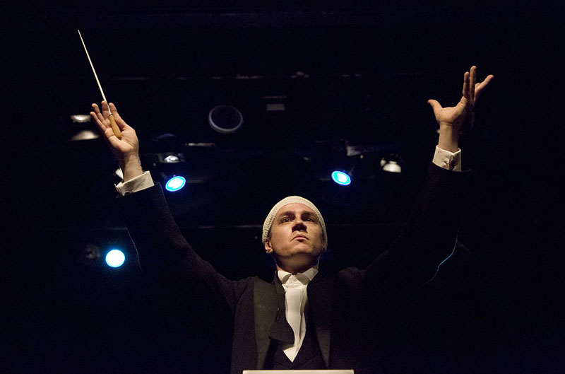 Conductor of Concerto played by Ryan O' Shea stands front and centre with his hands raised in the air whilst holding a conductor's baton.