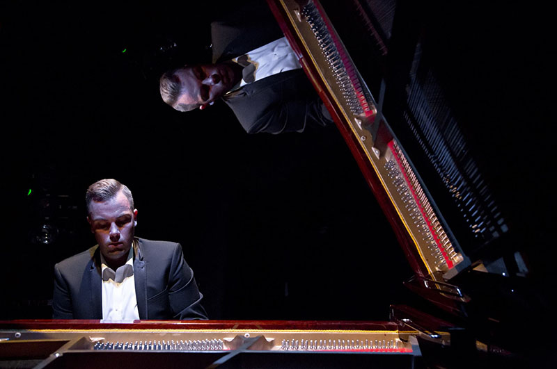 Mid-shot of a Nicholas McCarthy playing the piano, reflected in the piano lid