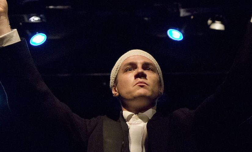 Performer Ryan O'Shea stands at the front centre of the stage, with a bandage wrapped around his scalp. He is holding a baton up as if to conduct an orchestra.