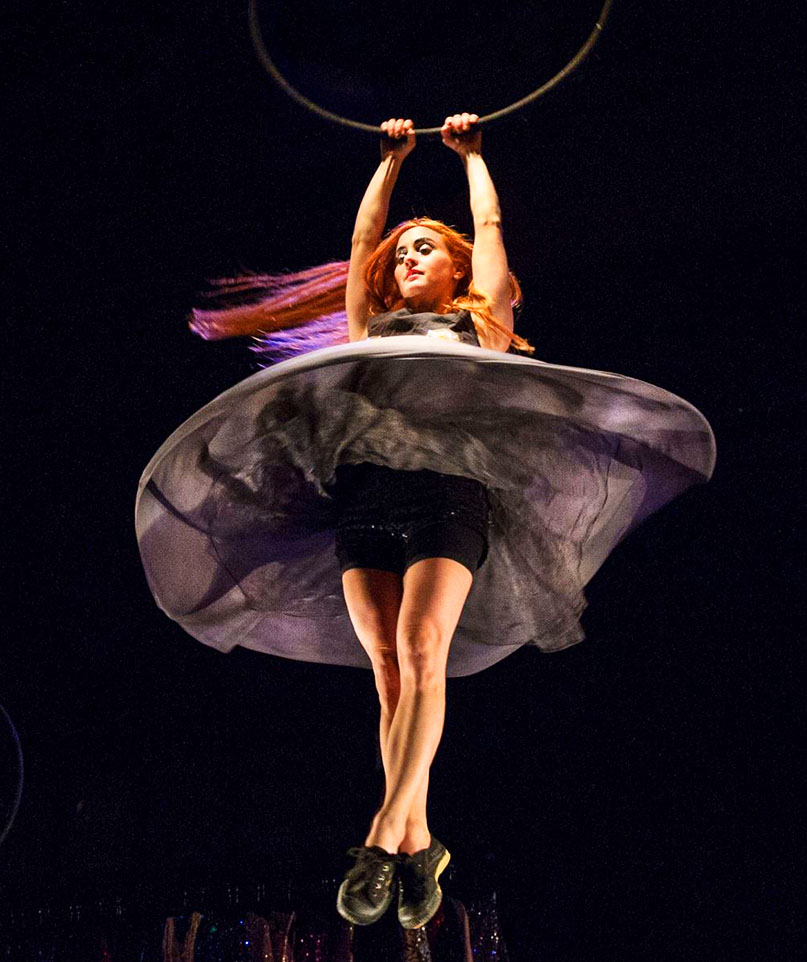 In the air, Sandy holds on to the bottom of a hoop as she spins round and round, making her dress flow upwards like a disc.