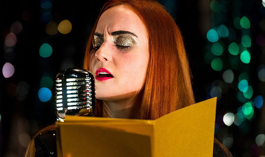 Against a green, glittery background Sandy, wearing gold glittery eyeshadow and bright red lipstick is singing into a classic-style microphone. Whilst she sings she is reading through a pile of letters.