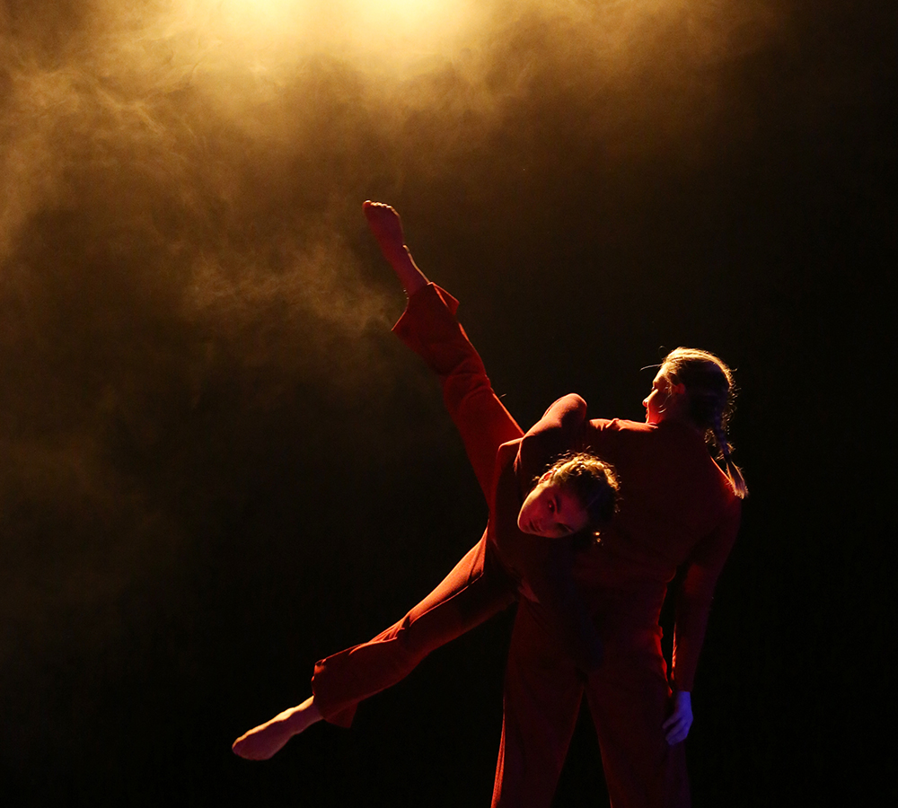 Two performers in a dimly lit, orange spotlight performing 'An Event' choreographed by James Wilton at The New Adelphi Theatre. Both performers are wearing red long sleeved leotards and red trousers. One performer is carrying the other one in the air.