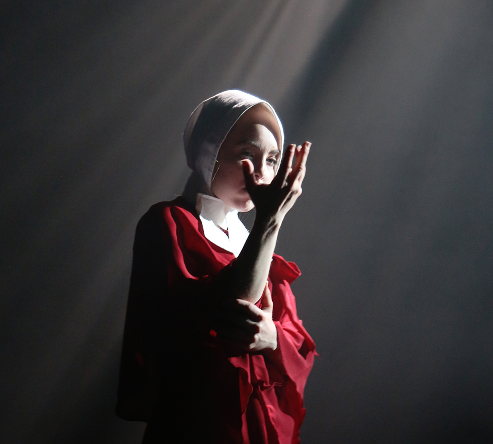 A performer from Emergence is stood in a white spotlight on stage, looking at her hands solemnly. She is wearing a red poncho and white bonnet, similar to the characters from Margaret Atwood's 'The Handmaid's Tale'.