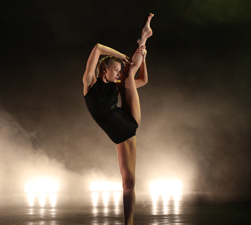 With bright, warm lights in the background of the stage, a performer from 'Emergence' dons a black leotard and is performing a classical ballet move on the stage in which she raises her leg almost above her head.