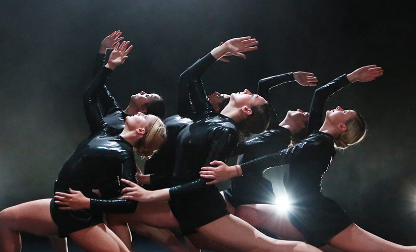 The ensemble of 'Emergence 19/20' performing on stage in black leotards