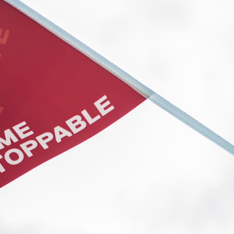 Become Unstoppable written on a red flag blowing in the wind