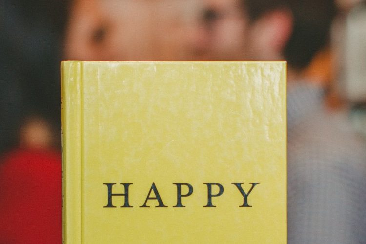 """Photograph of a book with """"Happy"""" written on the front cover, held up in front of a couple facing towards each other alongside some bookshelves"""