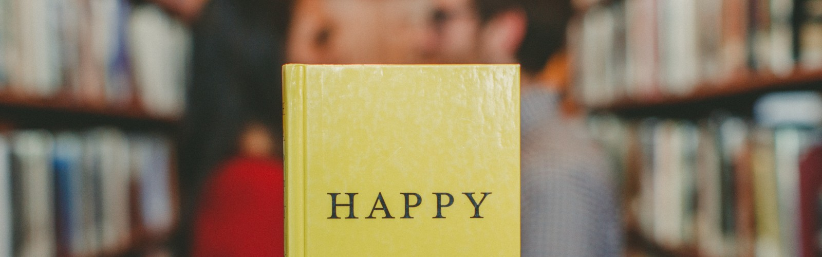 "Photograph of a book with ""Happy"" written on the front cover, held up in front of a couple facing towards each other alongside some bookshelves"