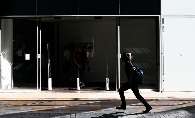 Image of the entrance to the University of Salford MCUK building, with a person walking across.