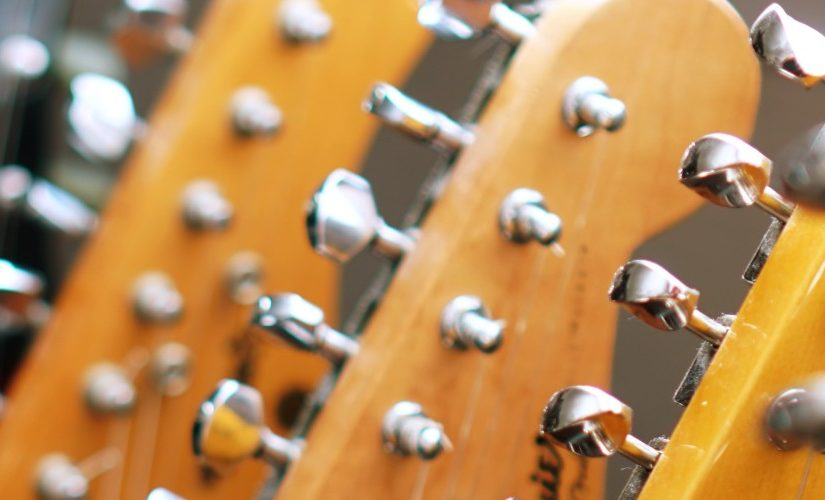 Image of the headstock and tuning pegs of several guitars