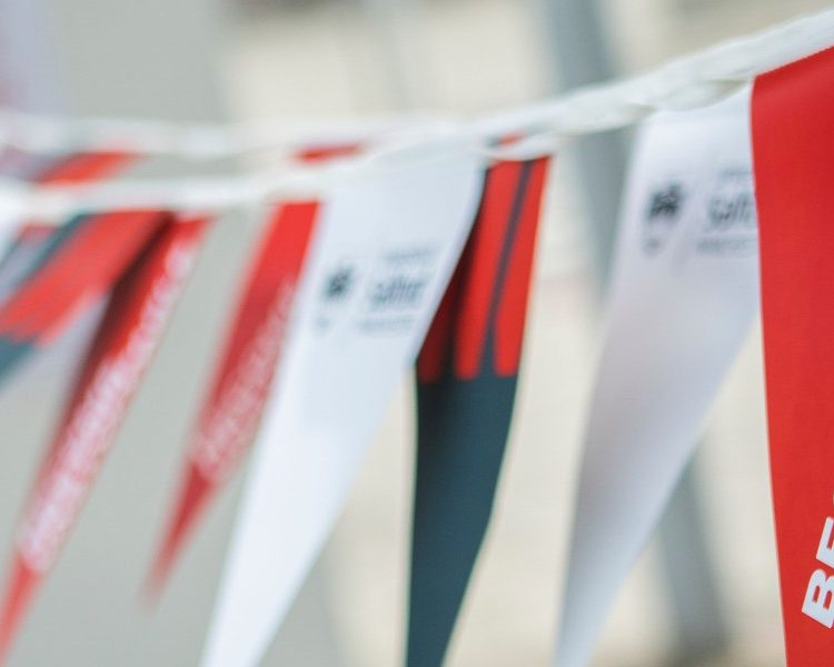 'Become Unstoppable' written on red, white and grey flags